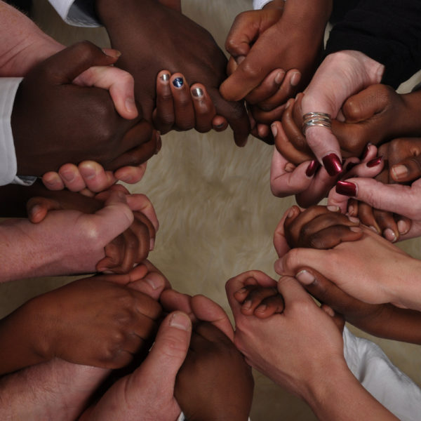 Several multi-ethnic hands locked in unity.
